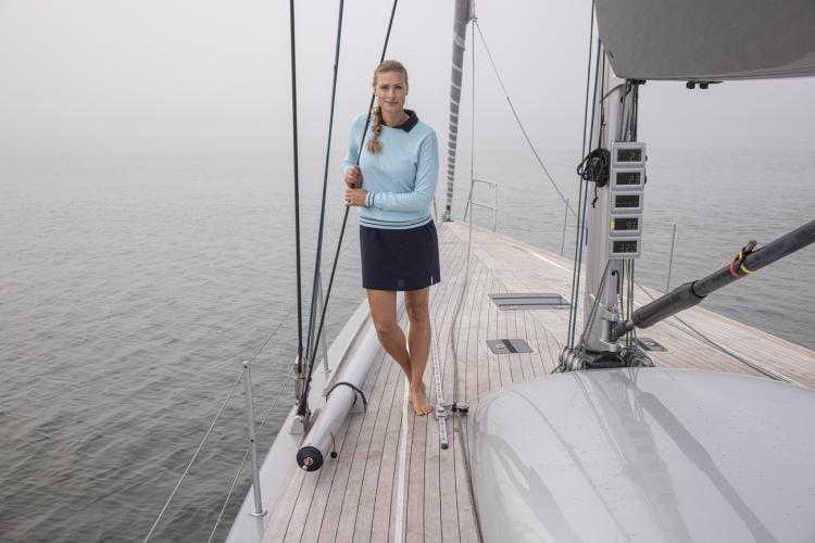 Summer Sweater fra Helly Hansen til dame i Cool Blue. Bildet viser genseren på en kvinne ombord på seilbåt
