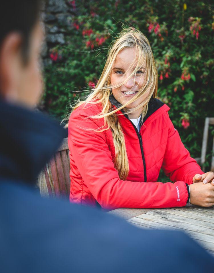 W Corsica Primaloft Jacket til dame fra Musto. Jakken er rød, og vises i miljøbilde på damemodell som sitter ved et bord