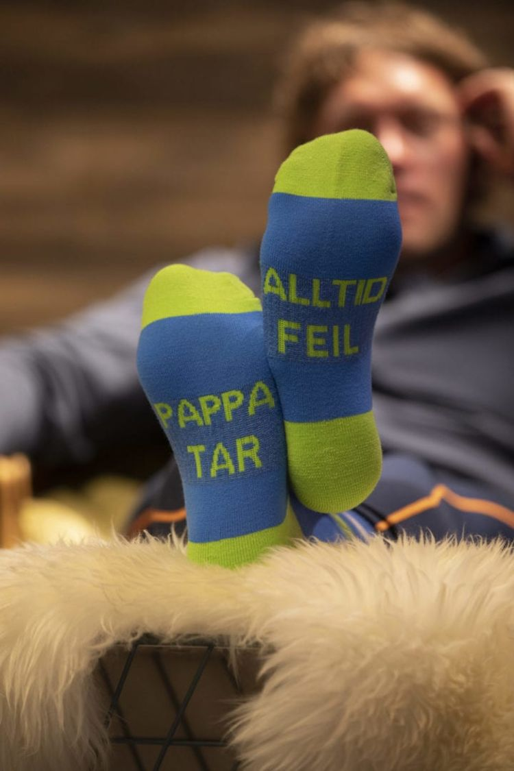 ullsokk fra house of hygge med teksten pappa tar alltid feil Bildet av person i godstol med sokkene på