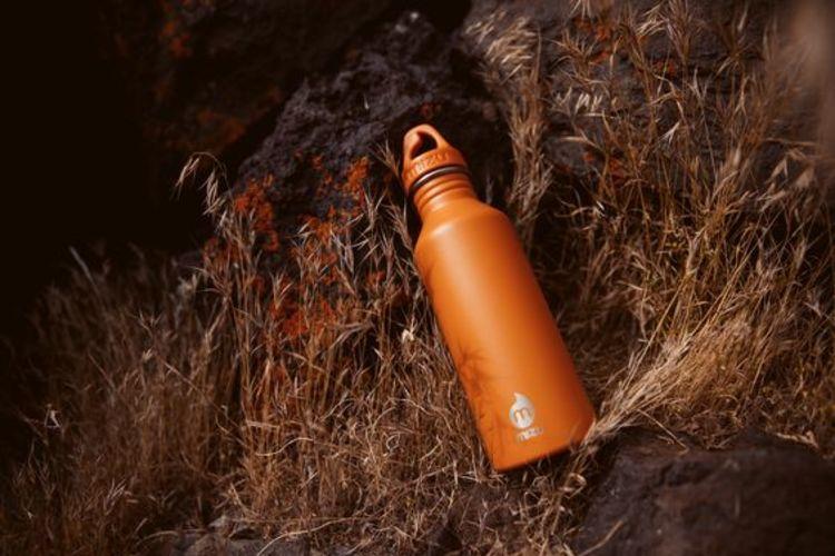 Drikkeflaske fra Mizu M8 i fargen burnt orange. Bildet viser flasken ligge på bakken