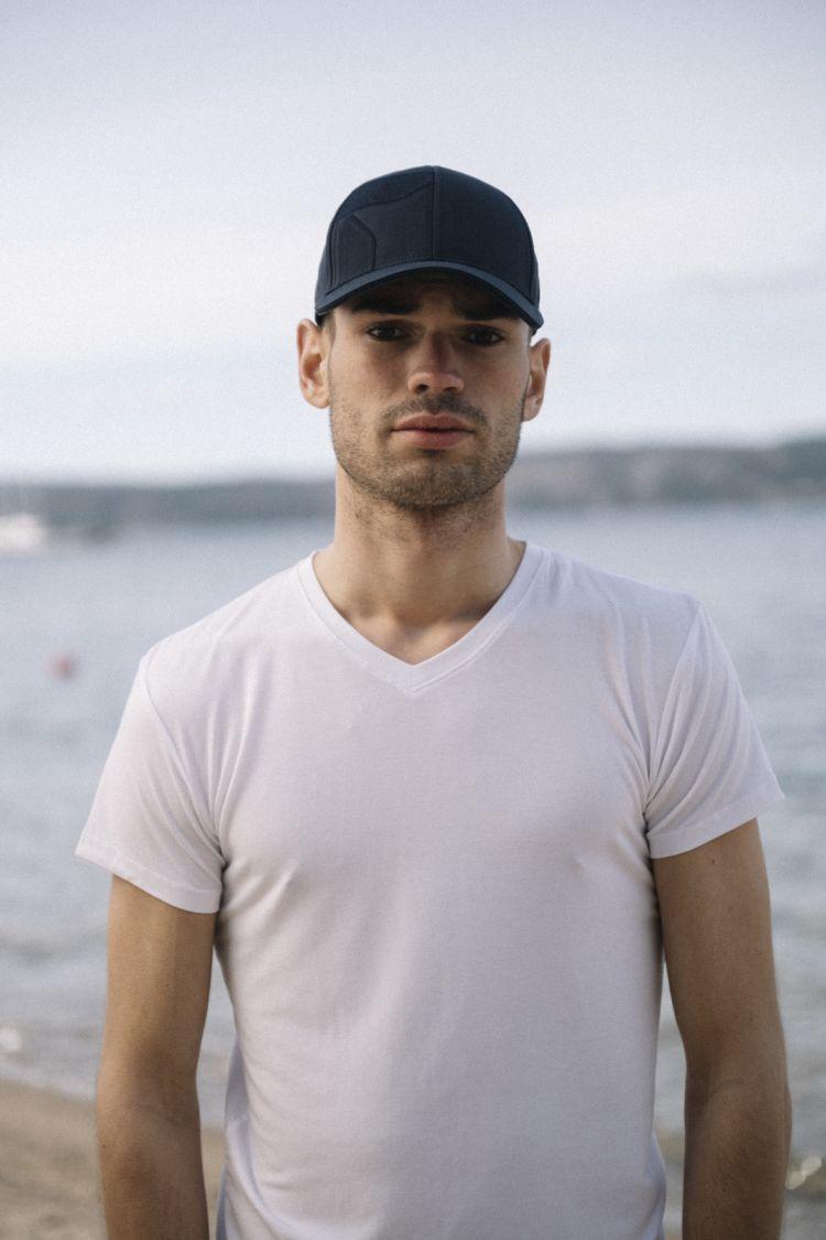 Mens v-neck t-shirt til herre fra Tufte Wear i fargen Bright White. Tskjorten vises på mannlig modell på stranden med caps fra Tufte