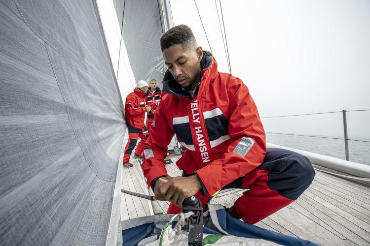 Salt Coastal Jacket fra Helly Hansen til herre i fargen Alert Red. Bildet viser jakken på modell ombord på seilbåt