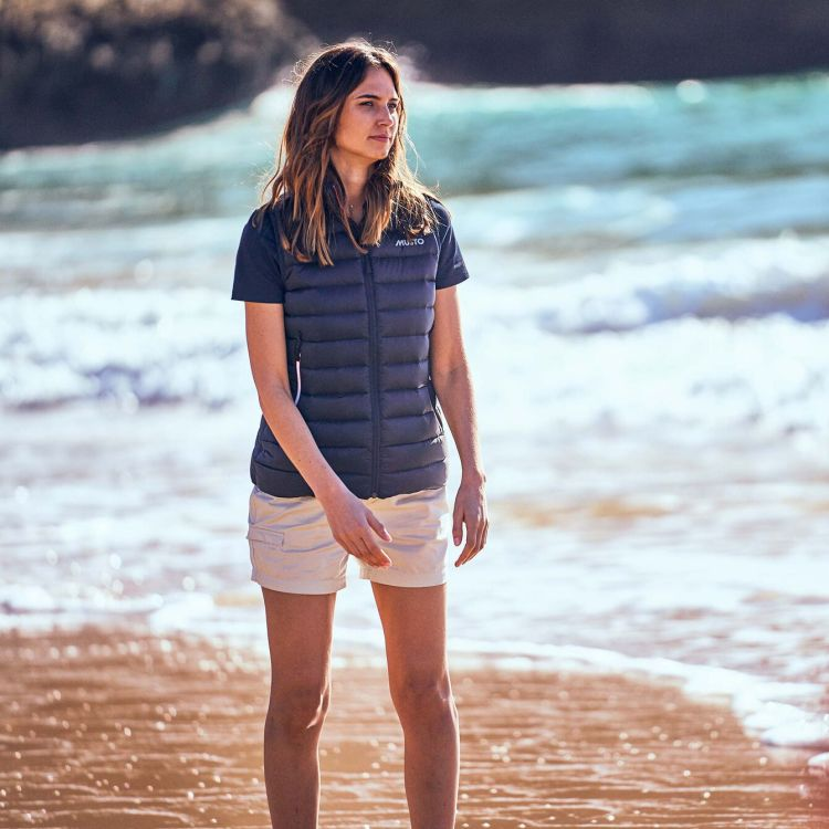 Tack Cotton Shorts fra Musto til dame i fargen White. Bildet av shorts på dame gående på stranden