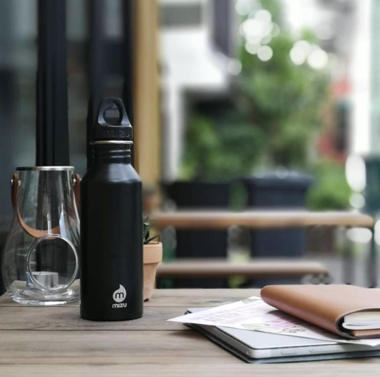 Drikkeflaske fra Mizu M8 i fargen svart. Bildet viser flasken stå på et bord på restaurant