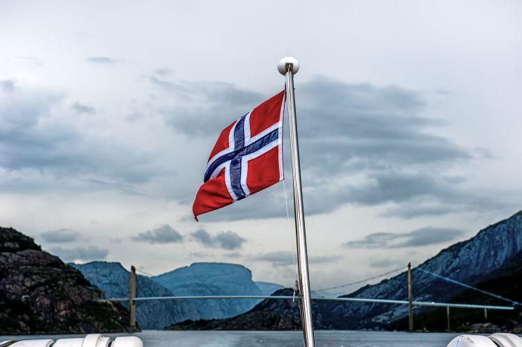 norsk flagg på båtstang. hav og fjord. Sydde norske flagg