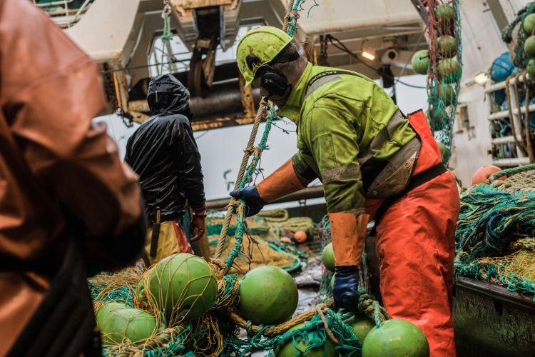 Fisker i orange oljekleder arbeider med fiskegarn