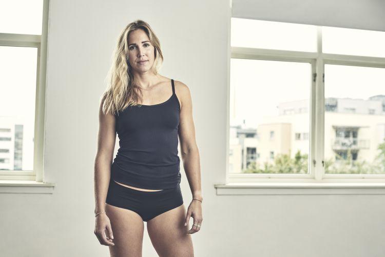 Singlet til dame fra Tufte Wear i fargen Black Beauty. Bildet viser singleten på en kvinne som står ved vinduer