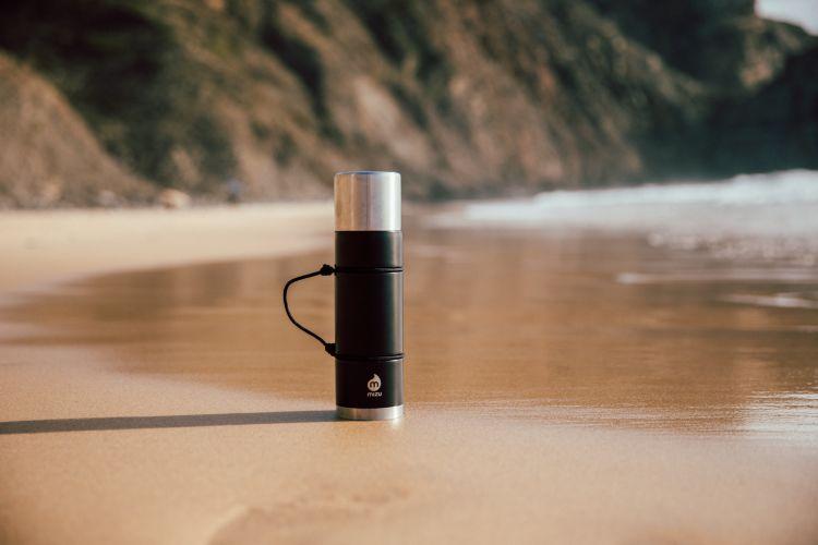 Termos fra Mizu i fargen black. Bildet viser termosen stående på en strand