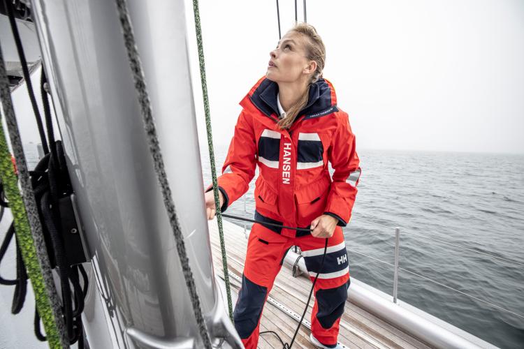 W Salt Coastal Jacket for dame fra Helly Hansen i farge alert red. Bildet viser dame ombord på seilbåt med SALT Coastal jakke og bukse i alert red