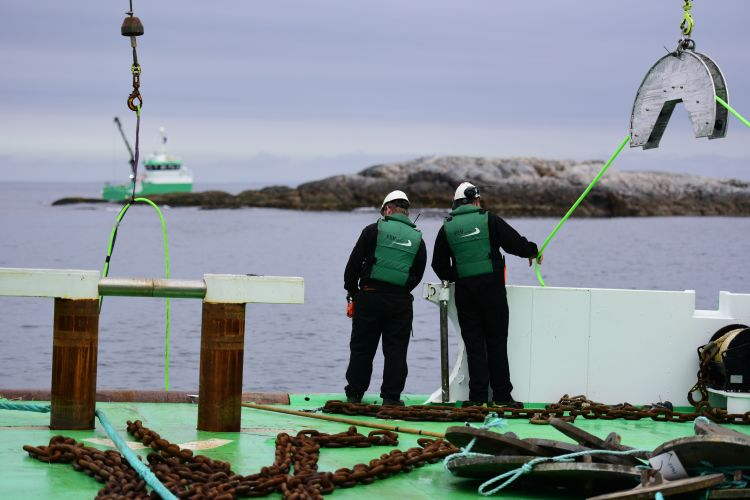 To menn på servicebåt ankerhåndtering