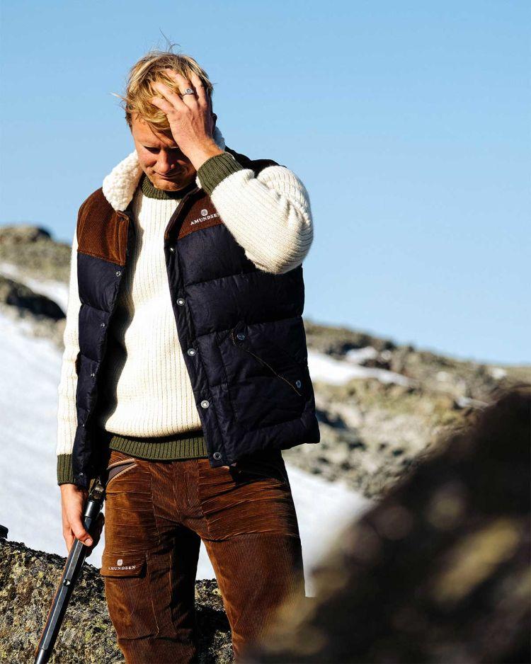 Groomer vest fra Amundsen Sports til herre i blått. Bilde av vesten på modell i fjellet