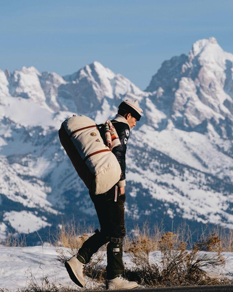okavanga duffelbag beige 65 liter. Mann bærer bag på vinterfjellet