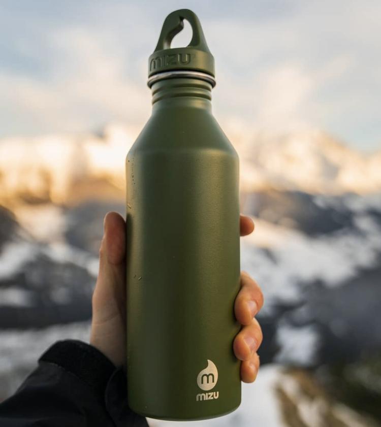 Drikkeflaske fra Mizu M8 i fargen army green. Bildet viser en hånd som holder flasken mot fjellbakgrunn