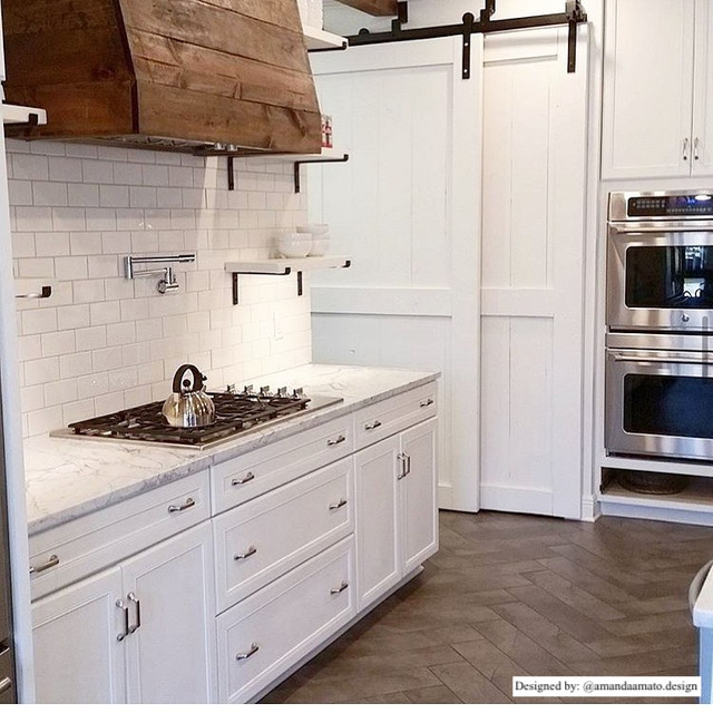 country chic farmhouse style kitchen with subway tile backsplash, wood stove vent, and white bypassing barn doors