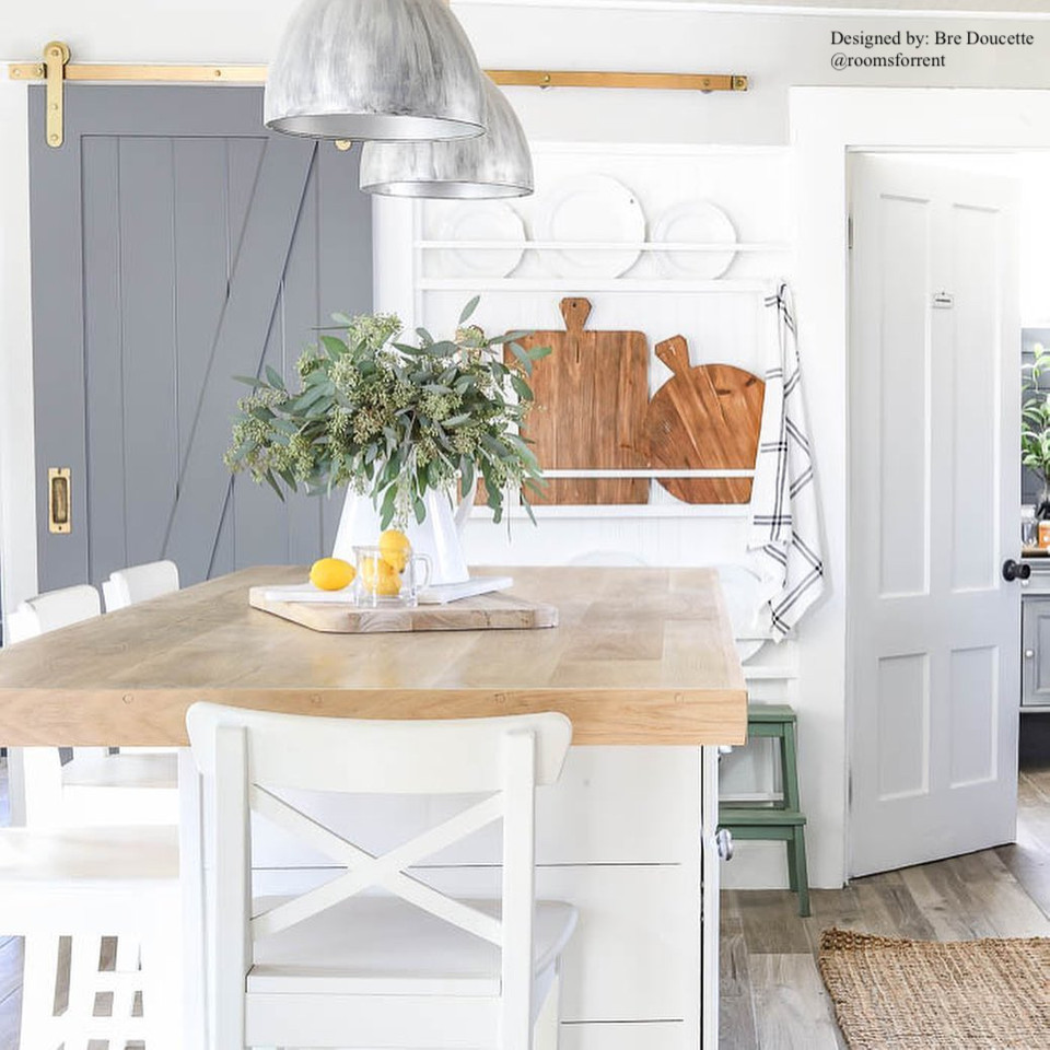 white and airy farmhouse style kitchen with butcher block counters and grey sliding bard door with brass hardware