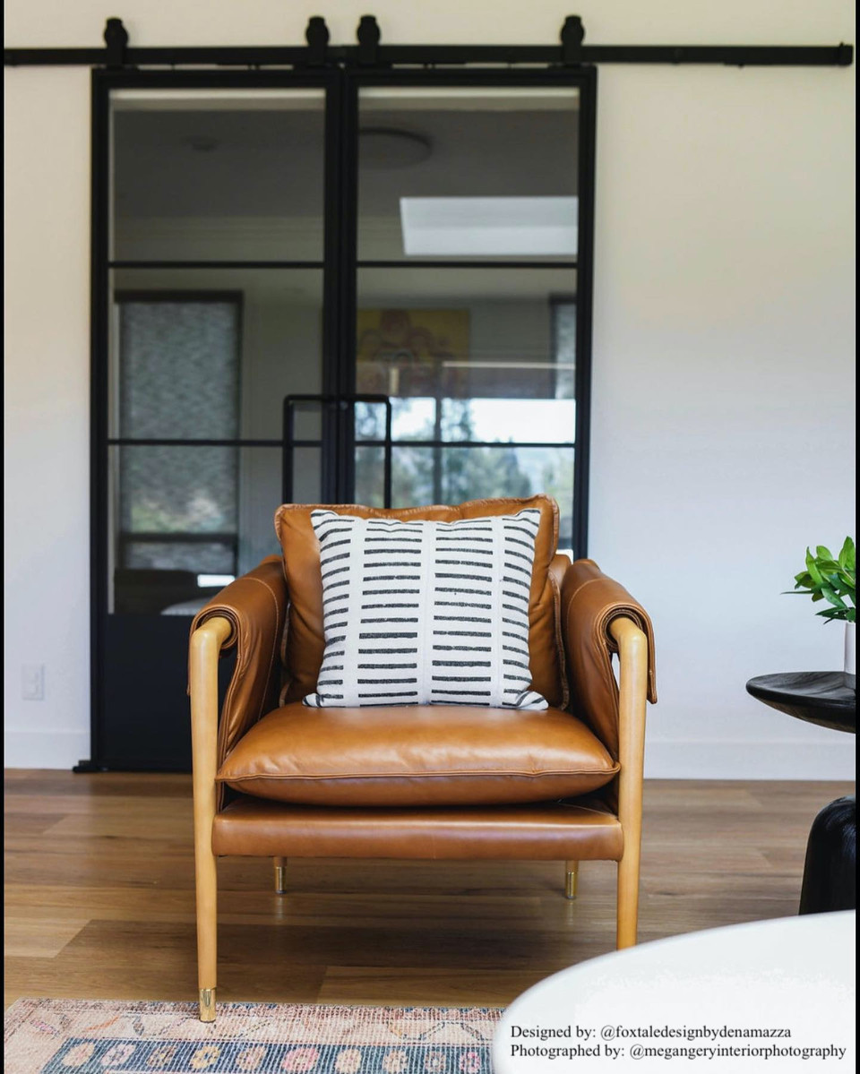 living room with a brown leather chair and metal sliding barn doors on the wall