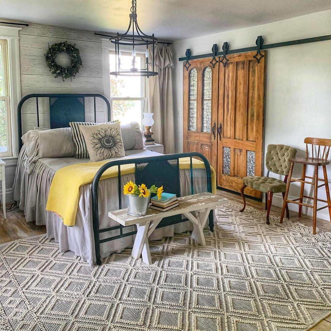 a hallmark worthy, farmhouse bedroom with antique vintage sliding barn doors.