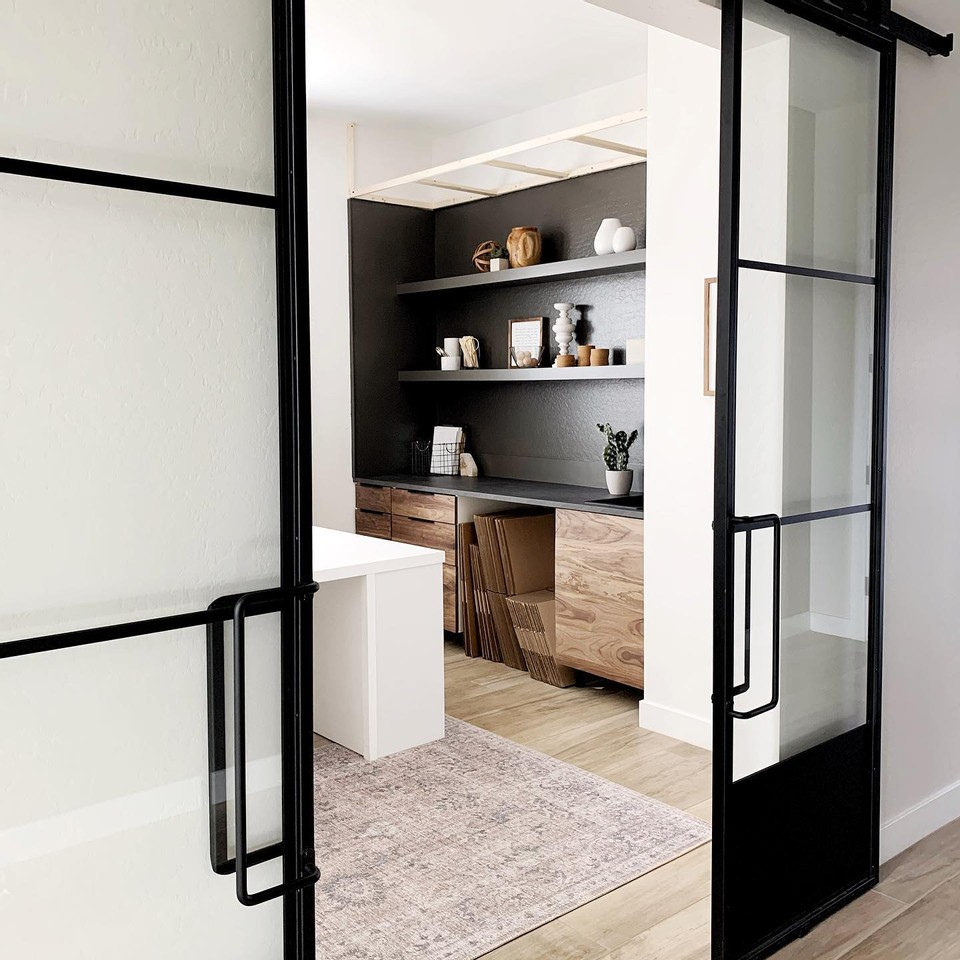 double french metal and glass barn doors opening up to an office with custom build grey shelves