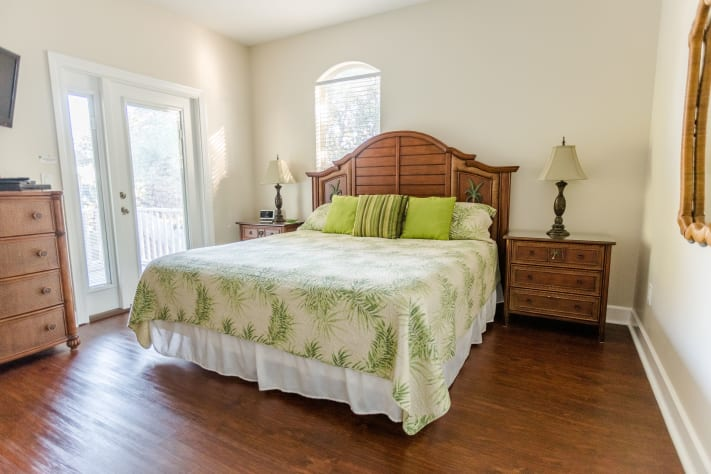 Second floor king bedroom with door to oversized porch overlooking huge yard