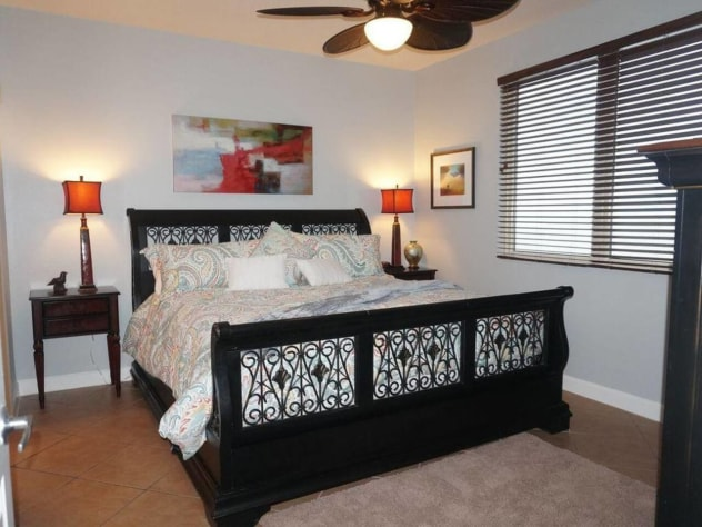 Master bedroom with king bed, full bathroom, TV, and a beautiful view of the beach/ocean.
