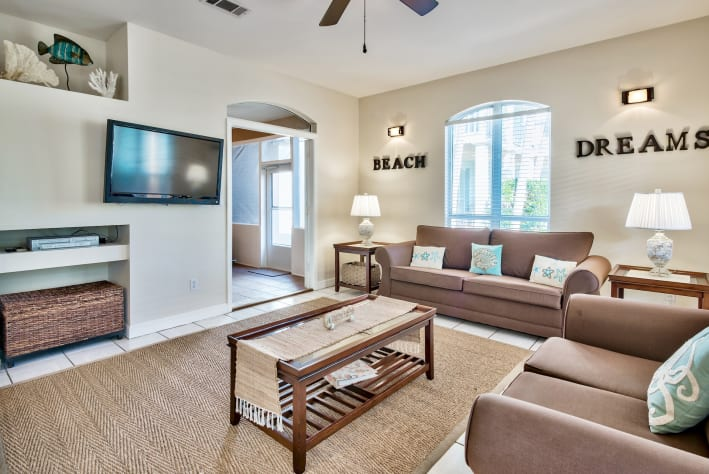 Living area with large flat screen tv and access to screened in porch