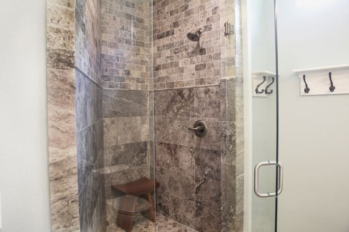 Travertine shower with teak bench