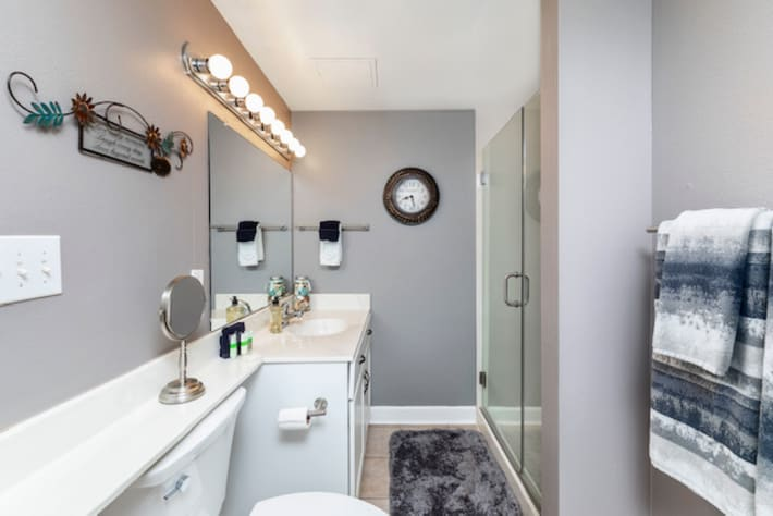 Guest room full bath with shower doors and ample storage.