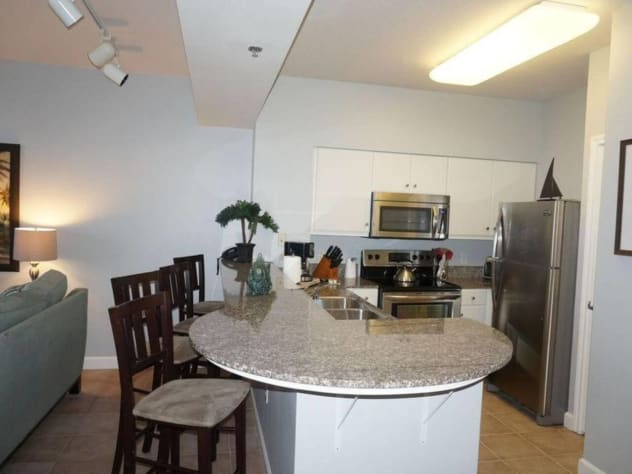 Kitchen with stainless appliances, granite countertops, and bar.