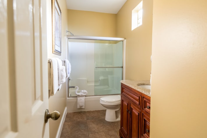 Second floor full bath with shower doors and updated vanity with granite