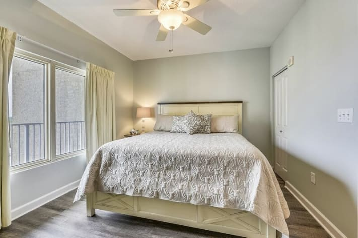 Master bedroom has king bed with beach theme decor