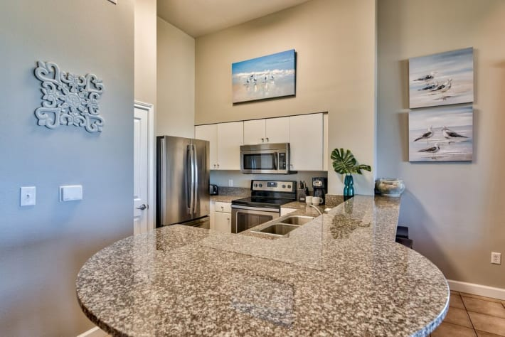 Granite counters, stainless steel appliances and white cabinetry