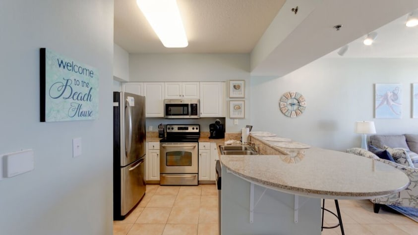 Granite counters and stainless appliances in the fully stocked kitchen