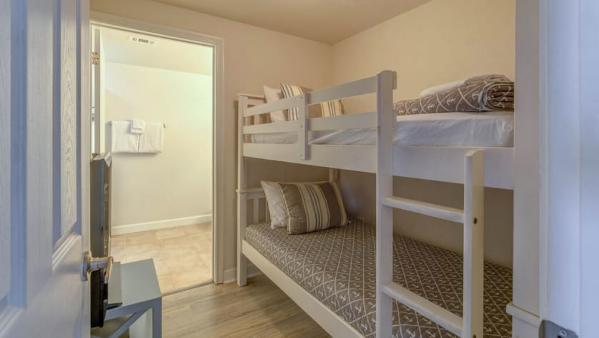 Bunk room with TV and door for privacy, as well as its own bathroom