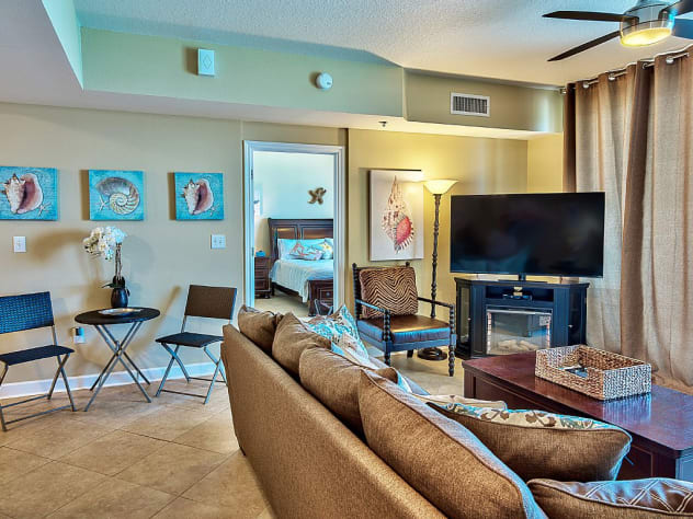Living area featuring Tommy Bahama fa, 55' flat- screen TV and ocean views.