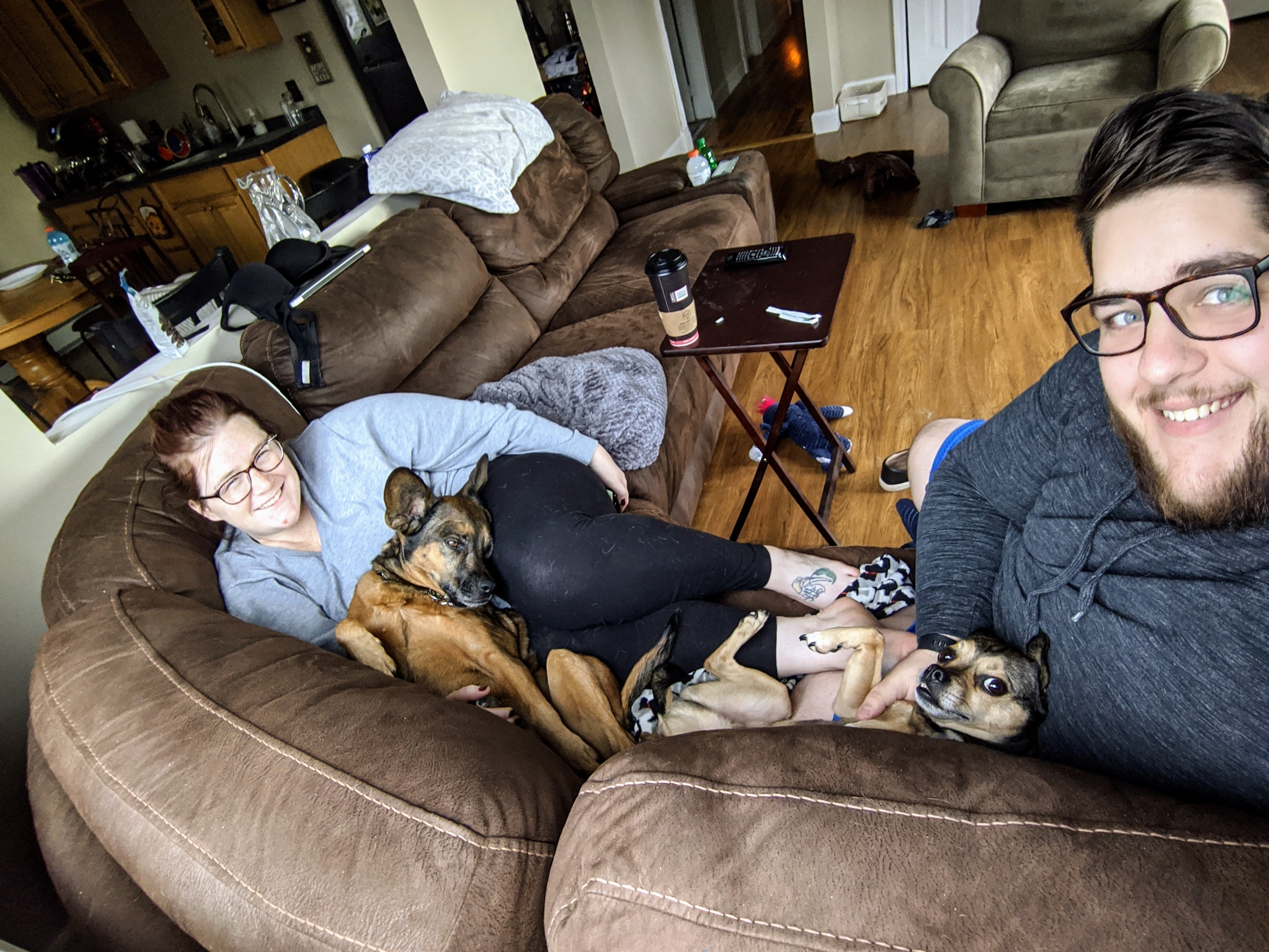 Megan and Ryan on a couch with their dogs, Maggie and Charlie
