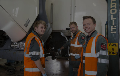 Three HGV technicians standing in front of a vehicle undergoing works