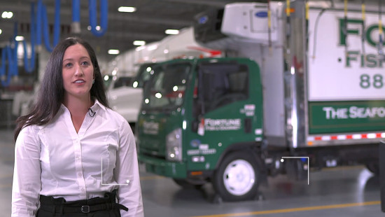 Woman speaking to the camera with a green refrigerated truck on the background