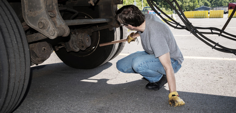 Driver checking truck tire pressure