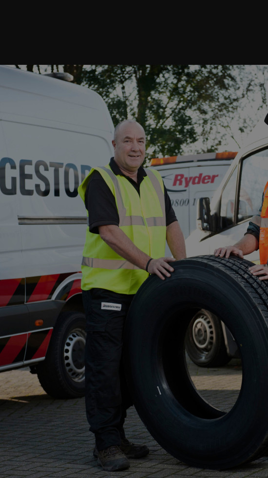Bridgestone and Ryder partnership depicted by an employee from each, in front of a tyre