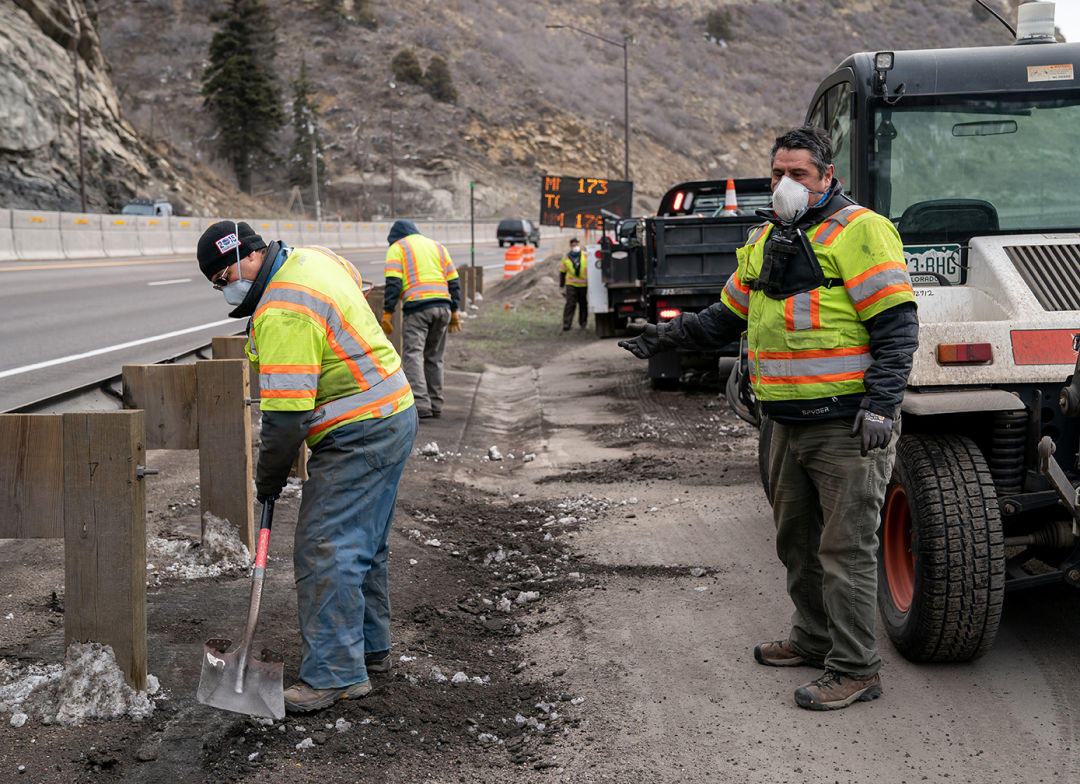 Workers wearing protective masks clear a roadside trail