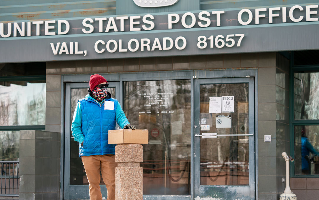 A person wearing a knit hat, balaclava, sunglasses, and gloves stands outside the Town of Vail Post Office with a package