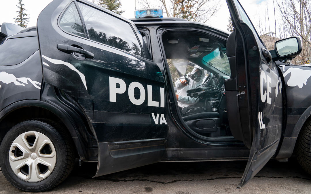A person wearing white protective gear sprays the interior of a police car