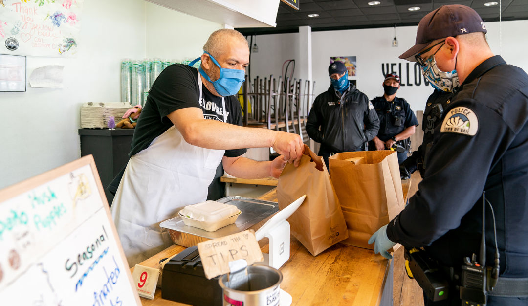 Police officers purchase food at a restaurant in Vail