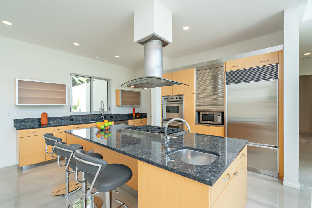 An eat-in kitchen with marble countertops and maplewood cabinetry