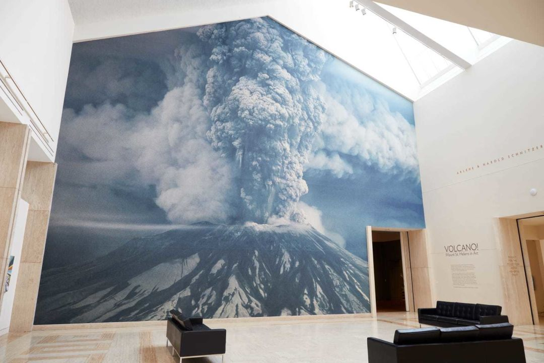 A large photograph of Mount St. Helens erupting opens the Volcano! Mount St. Helens in Art exhibit at the Portland Art Museum