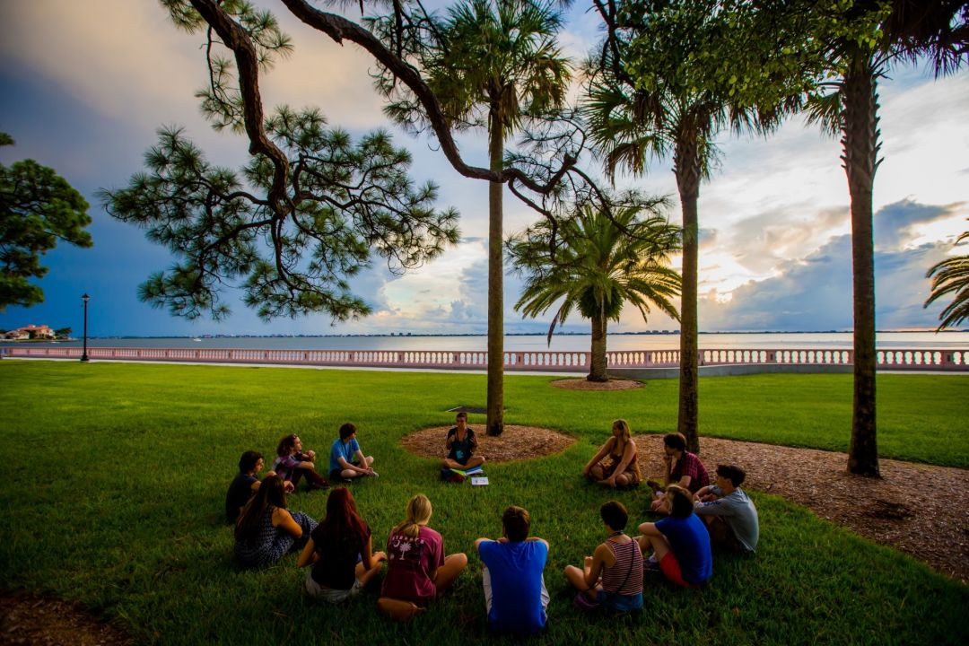 New College students gather in a circle on the college's lawn on Sarasota Bay.