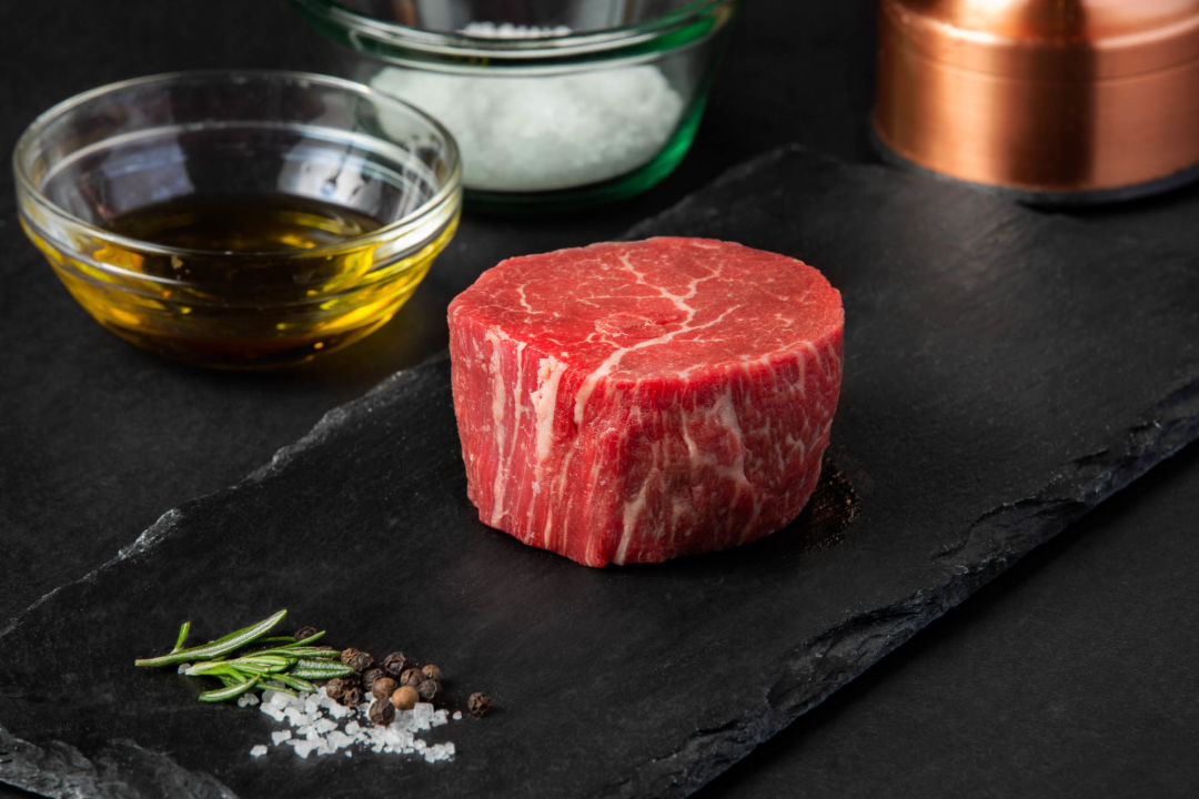Prime cut of uncooked steak on a slate board