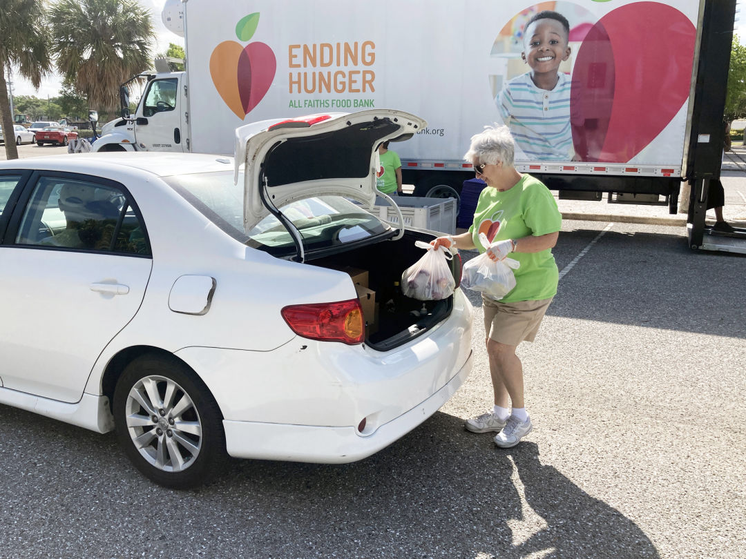 All Faiths Food Bank volunteer Maureen Donahue helps to load food into a community member's car during the May food distribution at Van Wezel