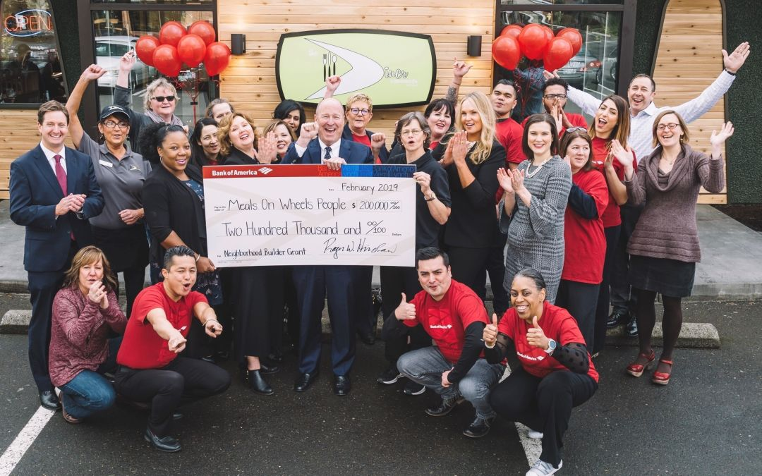 A group of people celebrate with a giant check representing a donation from Bank of America to Meals on Wheels People