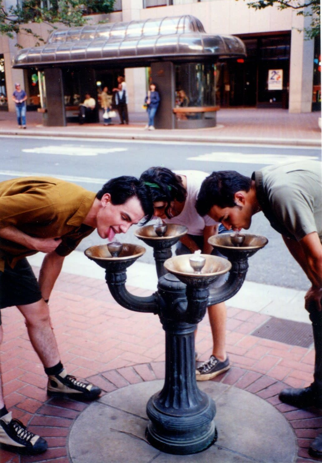Three people lean over a Benson Bubbler water fountain on a downtown street with a bus shelter behind them